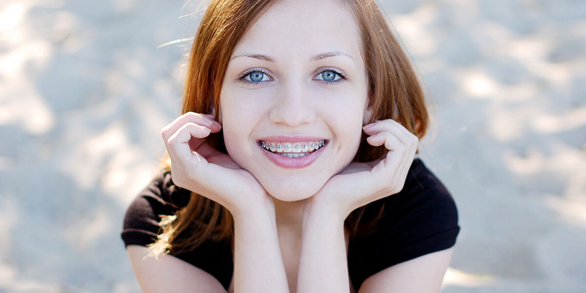 Smiling young lady in braces holding her face in both hands